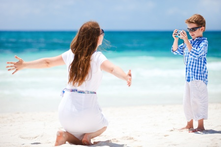 photographing: Little boy photographing his mother at tropical beach