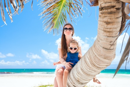 Mother and daughter sitting on palm at Caribbean beach photo