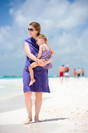 Young woman and her little daughter walking along beach photo