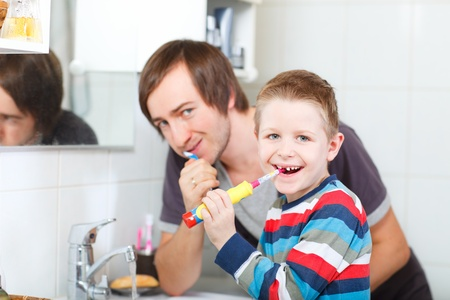 Father and son brushing teeth in bathroom photo