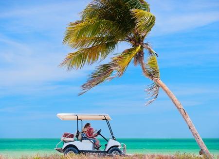驾驶高尔夫球推车的家庭沿热带海滩