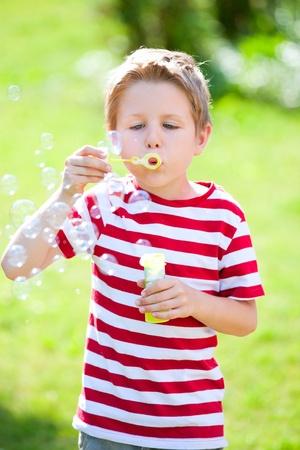 Cute caucasian little boy blowing soap bubbles photo