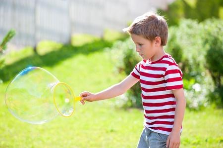 Cute caucasian little boy making soap bubbles photo