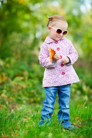 Cute little girl in a park at sunny fall day photo