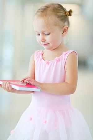 Portrait of little ballerina in dancing school photo