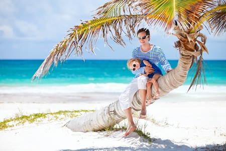 human palm: Father and daughter sitting on palm tree enjoying beach vacation