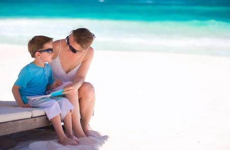 Mother and son reading book at tropical beach photo