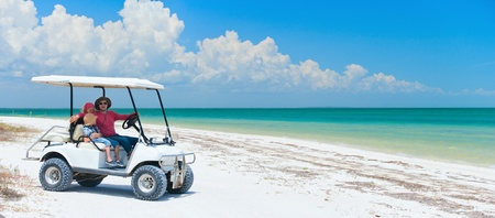 getaways: Family driving in golf cart along the tropical beach