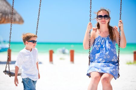 Mother and son swinging with tropical beach on background photo