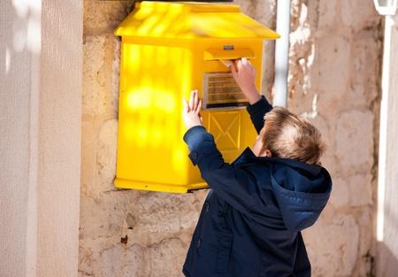 buzon: Muchacho se pone la carta en amarillo buzón Foto de archivo
