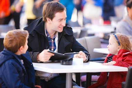 Young father and his two kids at outdoor cafe on autumn day photo