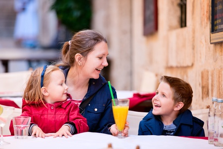 Young mother and her two kids at outdoor cafe on autumn day photo