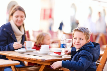 Young mother and her two kids at outdoor cafe on autumn day Stock Photo - 11197834