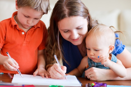 daycare: Young mother and her two kids drawing together Stock Photo