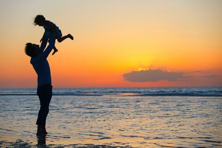 父と夕暮れ時のビーチで小さな娘のシルエット 写真素材