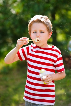 Cute caucasian little boy blowing soap bubbles photo