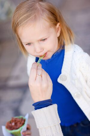 Portrait of cute little girls outdoors eating ice cream photo