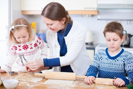 Young mother and her two kids at kitchen baking cookies photo