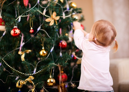 decorating christmas tree: Back view of toddler girl decorating Christmas tree