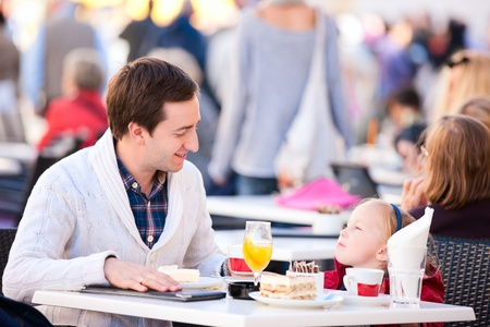 Young father and his little daughter at outdoor cafe on autumn day photo