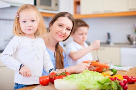 Niños ayudando: Joven madre y sus dos hijos haciendo ensalada de verduras
