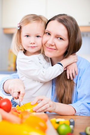 Young mother and her adorable little daughter making salad photo