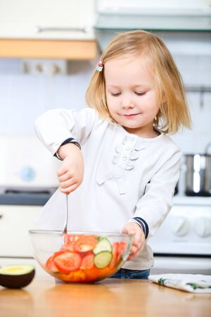 Portrait of adorable little girl helping at kitchen with salad making photo