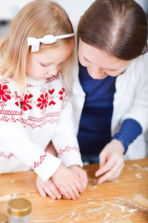 Young mother and her little daughter at kitchen baking cookies photo