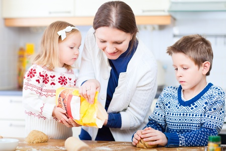 Young mother and her two kids at kitchen baking cookies Stock Photo - 11840183