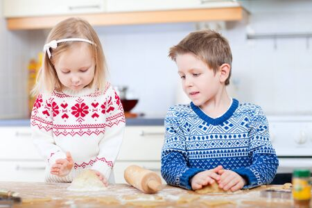 Two little kids baking Christmas cookies photo