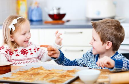 Two little kids having fun while baking cookies photo