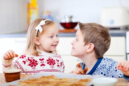 Two little kids having fun while baking cookies photo