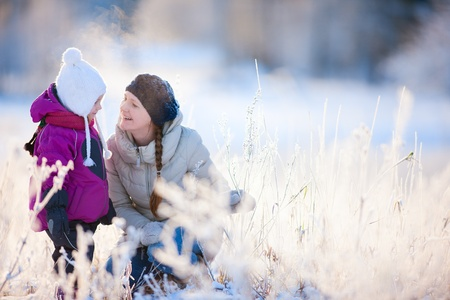 Young mother and her little daughter enjoying beautiful winter day outdoors Stock Photo - 11976187