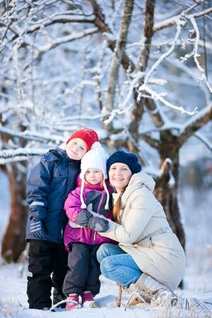 Beautiful mother and two kids outdoors on winter day photo