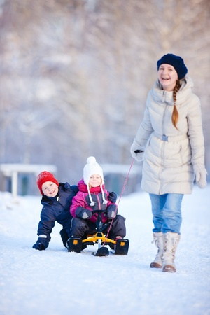 sledging people: Mother and two kids outdoors on beautiful winter day. Focus on kids