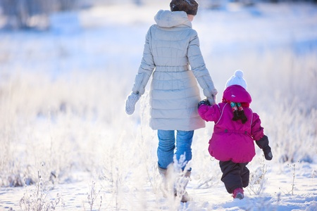 winter day: Back view of mother and daughter walking on winter day