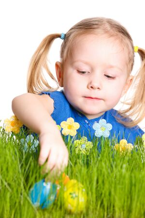 Adorable little girl looking for Easter eggs hidden in a grass photo