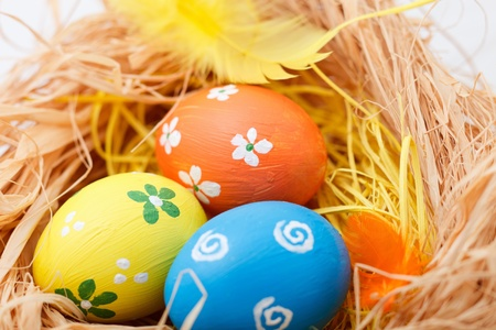 Painted colorful Easter eggs in a nest photo