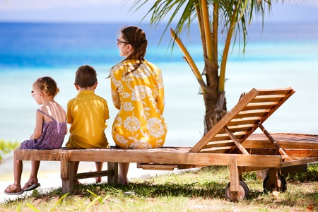 Young mother and her two kids enjoying ocean view photo