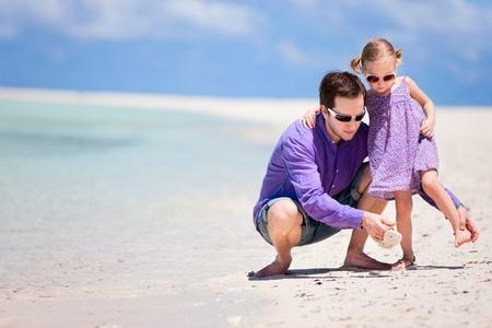 Joven padre y su hija adorable en la playa tropical