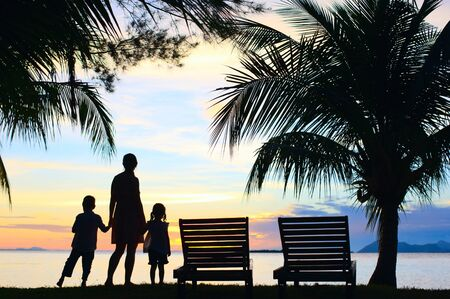 Silhouettes of mother and two kids at sunset on tropical island photo