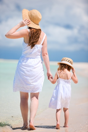 Back view of mother and daughter walking on beach photo