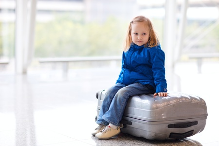 Adorable little girl at airport sitting on suitcase photo
