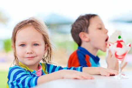 Two little adorable kids eating ice cream photo