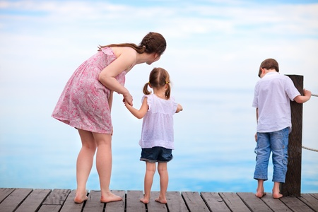wooden dock: Mother and two kids  looking for fish from wooden dock Stock Photo