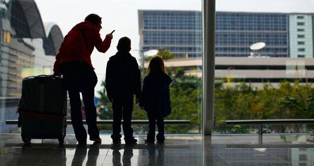 Mother and two kids with luggage standing near window at airport photo