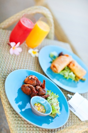 Two plates of delicious asian food and two glasses of fresh juices photo