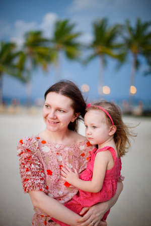 Portrait of adorable girl and her mother enjoying sunset photo