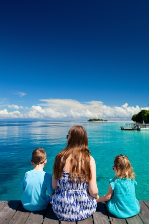 Back view of mother and kids sitting on wooden dock Stock Photo