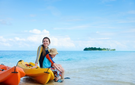 Happy mother and son after kayaking relaxing at beach Stock Photo - 12981550